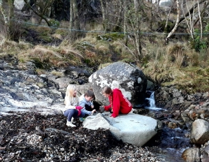Children playing on a rocky beach
