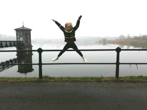 A little girl jumping in front of water.